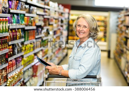 Smiling senior woman with cart using tablet in the supermarket
