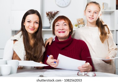 Smiling senior woman with daughter and granddaughter writing papers at home