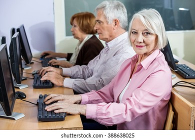 Smiling Senior Woman At Desk In Computer Class