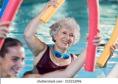 5a5165bbb46d3 Smiling senior woman doing aqua fitness with swim noodles. Happy mature  healthy woman taking fitness