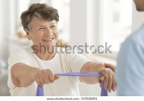 Lächelnde ältere Frau, die während der Fitnessklasse eine Kraftübung mit elastischem Band durchführt