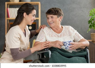 Smiling senior woman drinking tea and happy nurse in the hospice