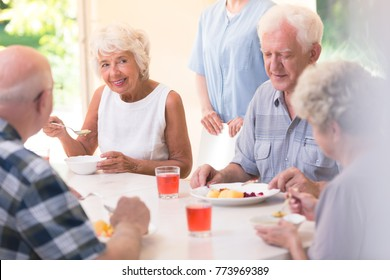 Smiling senior woman eating soup with friends while sitting at a table in the canteen