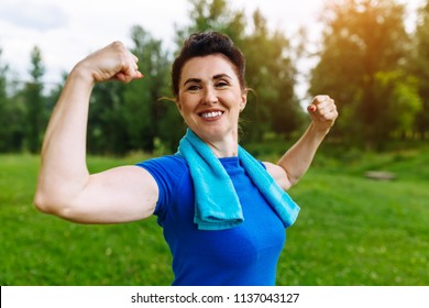 Smiling Senior woman flexing muscles outdoor in park. Elderly female showing biceps. Heathy life style concept. Copyspace.