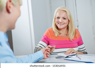 Smiling senior woman giving electronic health card to doctors assistant