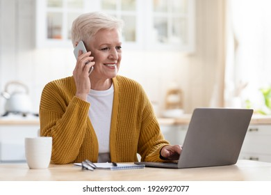 Smiling senior woman having conversation on phone, working on laptop in kitchen, drinking coffee, copy space. Beautiful old lady freelancer working from home, talking with clients on smartphone