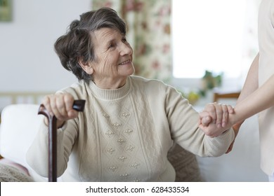 Smiling senior woman holding a cane and looking at her caregiver