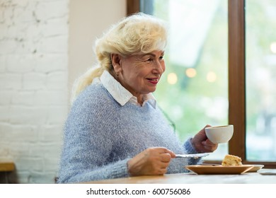 Smiling senior woman holding cup. Cake and coffee. Morning dessert in cafe.