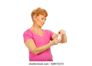 Smiling senior woman holding jar of pills