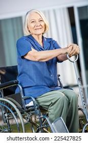 Smiling senior woman holding walking stick while sitting on wheelchair at nursing home yard