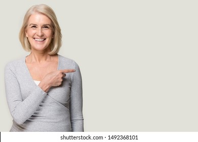Smiling senior woman isolated on grey studio background pointing with finger at blank copy space aside, happy positive aged female show at vacant advertising spot, recommend offer or service