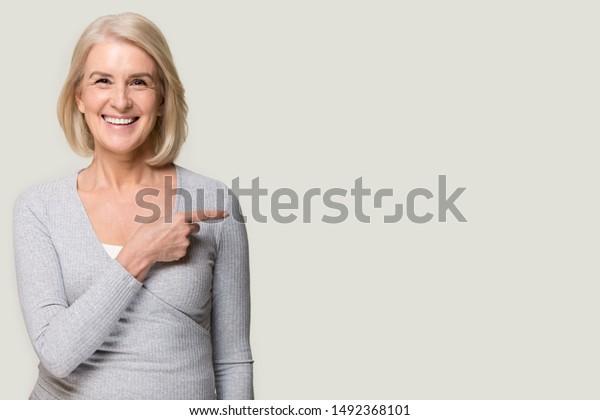 Lächelnde Seniorin einzeln auf grauem Studiohintergrund, die mit dem Finger auf den leeren Kopienraum zeigt, glückliche, positive weibliche Show an freien Werbespots, empfehlen Angebot oder Service