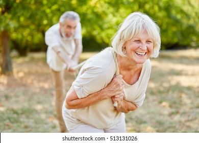 Smiling senior woman laughing and playing tug of war with a rope in the nature