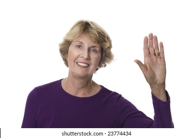 Smiling senior woman with left hand raised