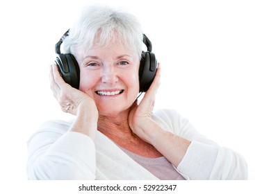 Smiling senior woman listening music with headphones against a white background