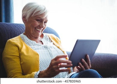 Smiling senior woman looking and laughing at her digital tablet in a sofa