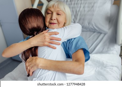 smiling senior woman lying in bed and hugging female doctor in hospital