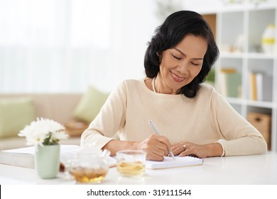 Smiling senior woman making notes in her diary