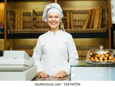Smiling senior woman offering fresh and tasty bread in bakery