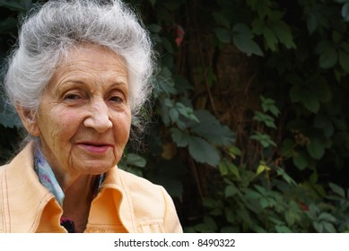 Smiling senior woman on green leaves background
