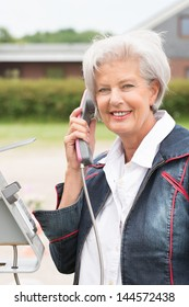 Smiling senior woman at the phone in front of a building