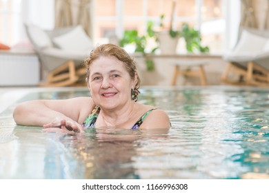 Smiling senior woman in the pool. Space for text
