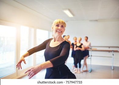Smiling senior woman practicing ballet in a dance studio with a group of friends in the background