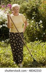Smiling senior woman with rake in the garden