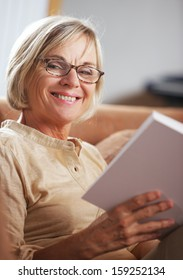 Smiling senior woman reading a book at home