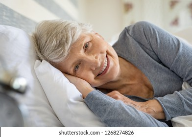 Smiling senior woman resting on bed and looking at camera. Awaken old woman with grey hair and pajamas in the early morning light. Portrait of elderly woman lying on side on bed and smiling.
