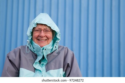 Smiling senior woman sheltering from the cold with hood up