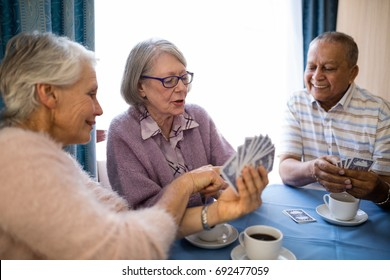 Smiling senior woman showing cards to friends while playing at table in nursing home
