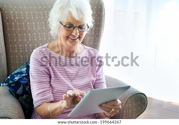 A smiling senior woman sitting in her couch holding a touchscreen