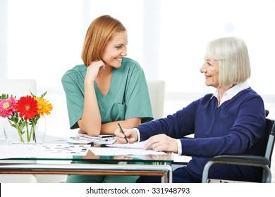 Smiling senior woman solving crossword puzzles next to nurse in nursing home