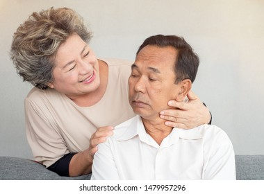 Smiling senior woman stand behind elderly man.  Loving wife comforting troubled husband. Concept of depressed, unhappy and reconcile.