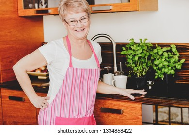 Smiling senior woman is standing in kitchen, domestic equipment behind.