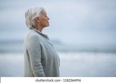Smiling senior woman standing on the beach