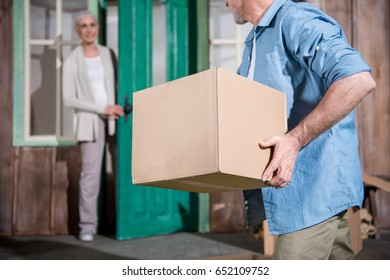 Smiling senior woman standing on porch of new house and looking at husband holding cardboard box