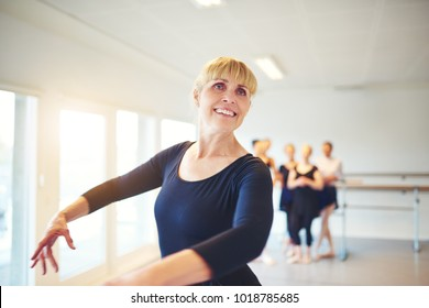 Smiling senior woman taking ballet lessons in a dance studio with a group of friends in the background