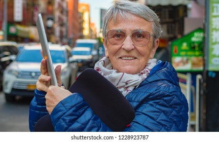 Smiling senior woman taking photos with a tablet on a busy city street.