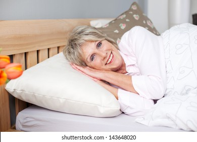 Smiling senior woman tries to fall asleep in bed with white linen
