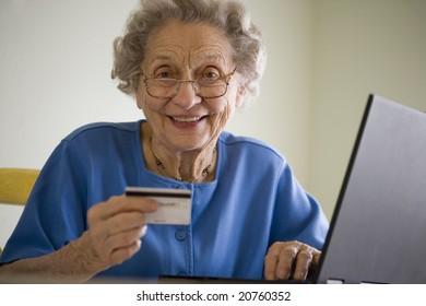 Smiling senior woman using credit card and laptop