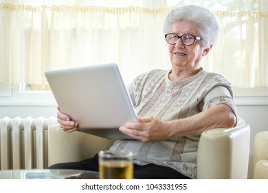 Smiling senior woman using laptop at home.