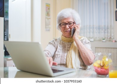 Smiling senior woman using phone and laptop at home.