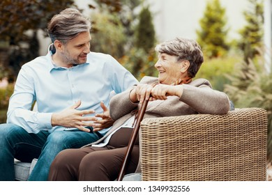 Smiling senior woman with walking stick listening to talking man on the terrace
