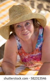 Smiling Senior woman wearing hat at beach on sunbed