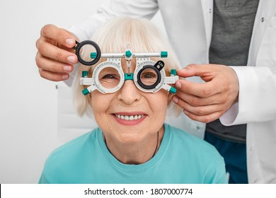 Smiling senior woman wearing optometrist trial frame at ophthalmology clinic. Ophthalmologist helping select glasses for treatment of vision. Eye check-up