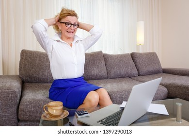 Smiling senior woman in white shirt and blue skirt 60-65 years old sitting on sofa at home, looking at laptop computer. Happy female holds hands behind head. Businesswoman with happy face expression