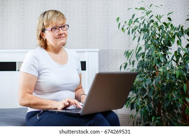 Smiling senior woman working on laptop at home
