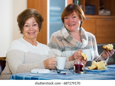 Smiling senior women having nice conversation while tea drinking